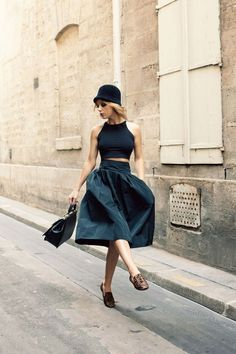 a full taffeta skirt, bare legs, smart leather bag and driving shoes