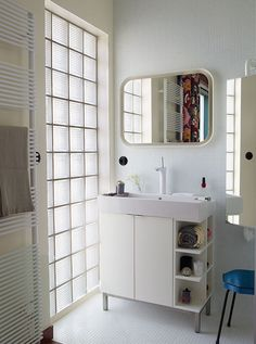 French bathroom with towel rack, IKEA mirror and cabinet, and secondhand stool