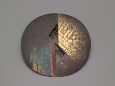 Round flat metal disk with colored and gilded decoration, pierced with two triangularopenings.