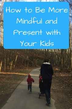 How to Be More Mindful and Present with Your Kids. (Photo: Man in a blue hoodie walking down a paved trail surrounded by trees pushing a stroller, with a child walking next to him.)
