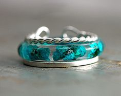 Unique set of stacking rings - listing is for all three rings:  Real turquoise tiny flowers incasted in eco-friendly resin. A plain sterling ring with mat finish and a twisted rope sterling ring.  The twisted rope ring is adjustable. Apart from wearing all three rings on one finger, this allows you to also wear this ring on a different finger or even wear this one as knuckle ring.  The other two rings are not adjustable, this is why you have to chose your size from the drop down menue.