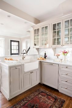 white marble counter + glass-front grey cabinets + rug