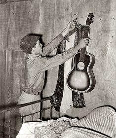 Guitar Hero: July 1939. Migrant boy removing guitar before family leaves for California. At old homestead near Muskogee, Oklahoma. Medium format safety negative by Russell Lee for the Farm Security Administration.