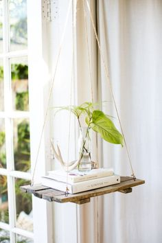 A hanging shelf in the bedroom allows us to add decor (plants, books and candles) without taking up precious square footage.""
