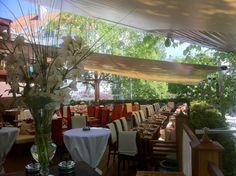 Bilde av utehagen til Sawan restaurant, ferdig dekket med blomster, duker og flotte seiltak.