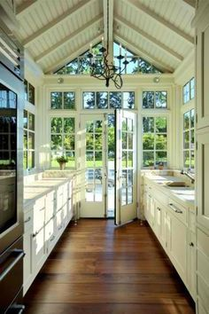 Great idea for condo or house downgrade...a small kitchen galley with lots of windows for light...also white cabinets and countertops with nice warm wooden floor