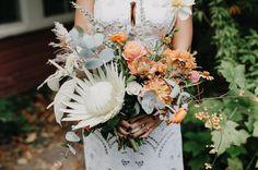 white protea bouquet with orange + antique roses