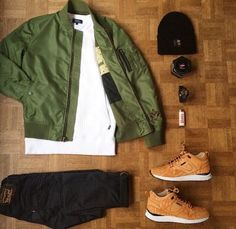 olive bomber. white crewneck sweatshirt. black jeans. tan leather sneakers. black beanie.