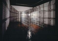 """Light Sentence at Centre Pompidou // By Mona Hatoum (1952 - ) // Treillis métallique, moteur électrique, minuteur, ampoule, câbles, fil électrique 36 unités de casiers en treillis métallique composant par leur juxtaposition une structure en forme de """"U"""". Une ampoule, suspendue au bout d'un fil au centre de la structure, varie lentement de hauteur, actionnée par un moteur électrique et projette des ombres mobiles en fonction de son mouvement."""