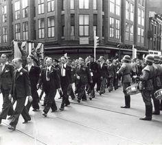 Défilé van mannen van het Nederlandse legioen die naar het Oostfront zullen vertrekken, met rechts Duitse soldaten met trommels. Nederland, 1941.