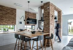 W wystroju kuchni postawiono na fragmenty z czerwonych cegieł również, np. na filarze czy na ścianachnad oknami. Zestawiono je z tak wyrazistymi elementami, jak meble czy dodatki w nasyconej czerni, co potęguje wyjątkowy charakter wnętrza.