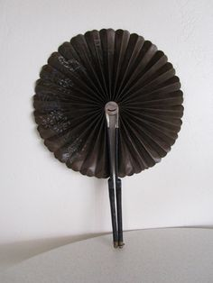 A fade from age black mourning fan patented in 1881 and with hand painted flowers decorating it. There were specific fans designed for mourning/funerals in the 1800's. Along with the black clothing they had beautiful black fans.