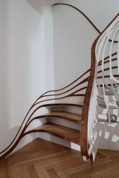 Staircase design with a curve resembling a wave flow line, giving the illusion that it is undulating as you walk through it. Designed by Atmos studio & made of oak.