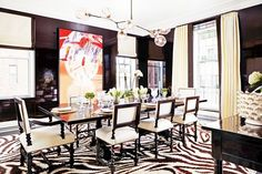 Dark dining space with black walls, a zebra print rug, and a modern chandelier