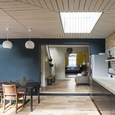 This extension to a Victorian house in London features a decorative wooden ceiling, exposed brickwork and a dining space that opens out to a garden