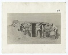 Old photo of a sod house in Kansas  (and men with an old ringer washer and a washboard, strangely enough)