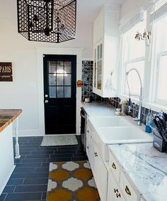 For this kitchen redo, the existing upper cabinets were salvaged and the lower cabinets rebuilt with Shaker-style doors and brass hardware found on eBay. The industrial-style faucet adds function to a classic-look farmhouse sink.