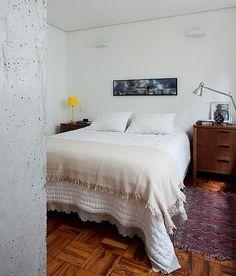 O teto de gesso deixou aconchegante o quarto, que é separado da sala pela estrutura de concreto aparente. Projeto do arquiteto Eduardo Chalabi