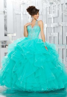 Turquoise Aqua Blue Dramatic and Elegant, This Quinceañera Ball gown Beautifully Combines an Intricately Beaded Bodice Featuring a Halter Neckline and Full Ruffled Skirt. Matching Bolero Jacket Included. Colors Available: Pink, Royal, Deep Aqua, White. Princess Ball Gown Sweet 15 Dress by Vizcaya | Morilee by Madeline Gardner. Style 89144.