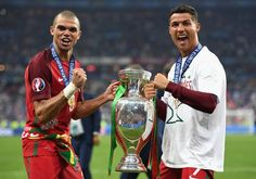 Cristiano Ronaldo and Pepe (L) of Portugal pose for photographs holding the Henri Delaunay trophy to celebrate after their 1-0 win against France in the UEFA EURO 2016 Final match between Portugal and France at Stade de France on July 10, 2016 in Paris, France.