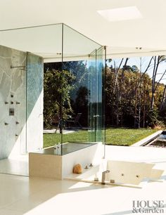 Glass shower and soaking tub open right up to the back yard.  Sally Hershberger's Los Angeles bathroom includes a glass-walled shower