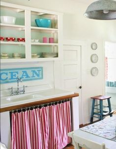 """Breezy looking seaside bungalow kitchen w/ open shelving, beautifully hung picnic print cabinet curtain, turquoise """"ocean"""" sign and color coordinated glassware. Grey Kitchen Curtains, Small Window Curtains, Diy Curtains, Kitchen Valances, Cosy Living, Cottage Living, Best Kitchen Cabinets, Open Cabinets, White Kitchen Sink"""