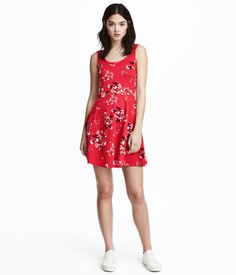 Red/floral. Short, sleeveless dress in thick jersey. Low-cut neckline at back, seam at waist, and flared skirt.