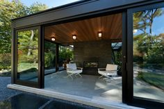 Two things. 1. Dark gray crushed rock for garden instead of brick patio, with large square slate. 2. Dark stone (brick?) fireplace like this in corner of living room. Glass House in the Garden - modern - patio - boston - Flavin Architects