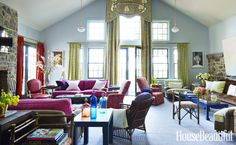 """In the new double-height living room, """"the eye gravitates to that fearless David Hicks flash of color — the fuchsia sofas that flank the fireplace,"""" says designer Jeffrey Bilhuber. They're covered in Malabar's Tabia. A French armchair is upholstered in Designtex's Parga. The exuberant blue-and-persimmon print on a pair of chairs is Tulu's Stella. Another sofa, covered in a corduroy from Sonia's Place, is placed against the old exterior wall of the icehouse. Curtains in Osborne"""