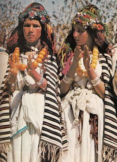 Berber girls clap to the rhythm of village musicians at a festival in the Atlas Mountains. The distinctively striped wool shawls they wear identify their clan affiliation. Art Marocain, Caucasian Race, Tribal Mode, Moroccan Jewelry, Tribal People, Folk Costume, Costumes, Tribal Fashion, African Women