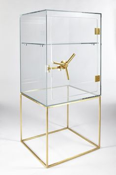 Precious design CtrlZak Storage furniture in transparent extra light crystal with mechanism and base in satin-finished brass. As a real safe, its protects the contents revealing the essence. A symbolic up-to-date object where everyone is free to decide what is worth guarding .
