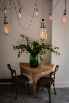 Assorted bulbs hanging from exposed ceiling joists, Ochre painted kitchen cabinets on polished concrete floor with fifty hanging bulbs in ceiling, British Standard Cupboards, Toni Halliday, Rachel Aspland | Remodelista