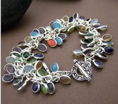 Glass and silver charm bracelet. Sterling toggle clasp. Great color and movement with this piece!