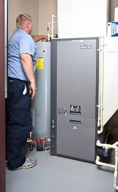 A technician inspects a geothermal HVAC air handler