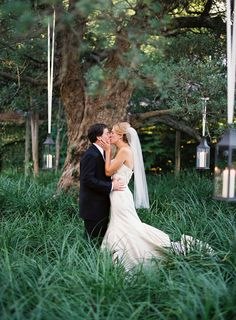 Trees and luscious grass with hanging lanterns. So romantic! via Southern Weddings
