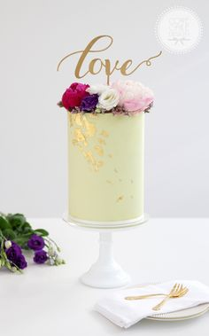 Tall buttercream cake with gold leaf and floral crown