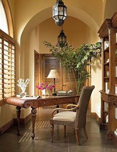 This workspace is so pretty. Love the archway and window, the desk and chair, and the bookshelves lining the wall.