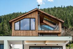 Die Fassadengestaltung des Einfamilienhauses zeichnet sich durch die Ausrichtung der Fenster aus, welche an die Ausblicke auf die umliegende Berglandschaft angepasst ist. Das Haus spiegelt dadurch eine Transparenz wieder, was der Idee eines offenen Lebensstils und einem gefühlvollen Umgang mit der Natur nahekommt. Im Herzen des Hauses werden alle Stockwerke durch eine offene Deckenkonstruktion miteinander verbunden, was im Innenraum ein Atrium entstehen lässt. Atrium, Flat Screen, Cabin, House Styles, Furniture, Home Decor, Room Interior, Windows, Mountain Landscape