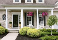 Inviting front porch with just enough space for all of the essentials: hanging and potted plants and rocking chairs.