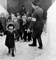 Escorting nursery children from an air raid shelter in 1942