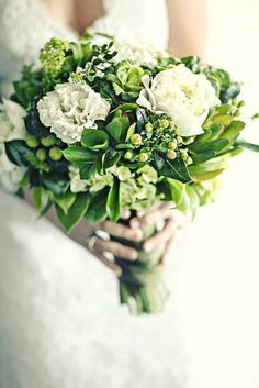 Jenn's bridal bouquet was created with green kale, Brazilian berries, viburnum, safari sunset, boxwood, white peonies and lisianthis, green hydrangea, sprigs of rosemary and Italian ruskus