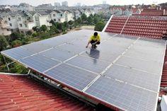 Trabalhador inspeciona painéis solares no teto de um edifício residencial em Yichang, na provícia chinesa de Hubei