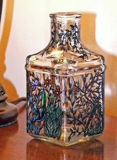 Hand Painted, Glass Vase with Flowers, Leaves, Trees and Vines. The Glass is prepared with a surface conditioner, painted with enamel and protected with a gloss glaze.