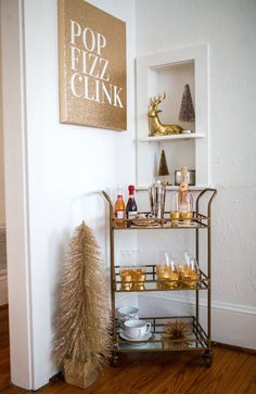 holiday bar cart, how to decorate your home for the holidays, haute off the rack, pop fizz clink art, gold reindeer, gold temples wine glasses, gold stemless champagne flutes, gold bar cart, mini christmas tree, holiday home decor, holiday party ideas,