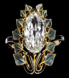 Diamond ring. The large diamond is set vertically along the bezel, framed within a border of green leaves on black stalks, with the shoulders also enamelled dark green by René Lalique c.1902-4.