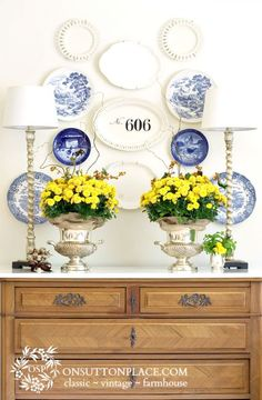 Fall Decorating with Mums. Forget the mums! Look at the plates and platters on the wall with the buffet lamps. Love that look.