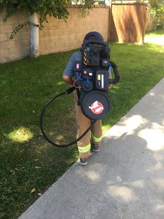 Ghostbusters DIY proton pack. Dollar store products: used black hose, cookie tin, plastic food storage containers, thick poster board, matte black spray paint & caution tape from Home Depot, & printed ghostbusters logo.