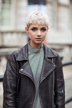 Kimmy in a distressed leather jacket, houndstooth plaid short, and cropped blonde bob.