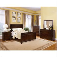 Dark brown wood bedroom furniture with dark smokey blue walls white bedding dark wood floor a Master bedroom with yellow walls
