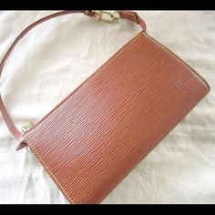 """Louis Vuitton Epi Pochette Wristlet Clutch Preowned. Cipango brown, (medium brown). Very good condition, looks well taken care of and rarely used. Epi leather looks great,interior lining is very clean. Date code: AR0929. Dimensions: 9.4"""" length, 1.2"""" depth, 4.9"""" height. Includes Louis Vuitton dustbag. Can be worn as a pochette, wristlet, or carried as a clutch. Additional photos upon request. Price is firm. No trades or Paypal. Louis Vuitton Bags Clutches & Wristlets"""